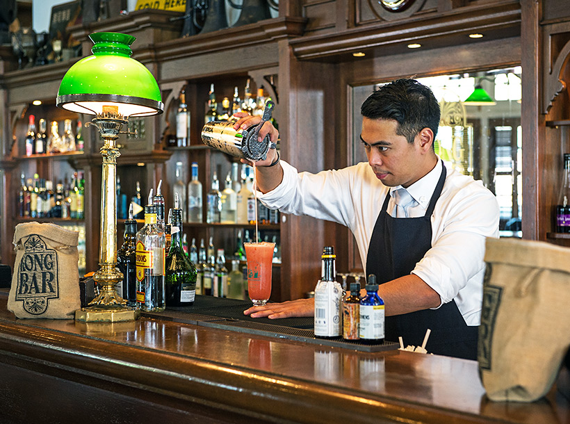 bartender creating a singapore sling cocktail at raffles singapore