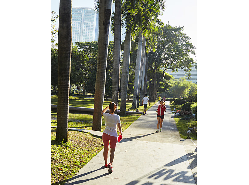 people walking and running through a city park