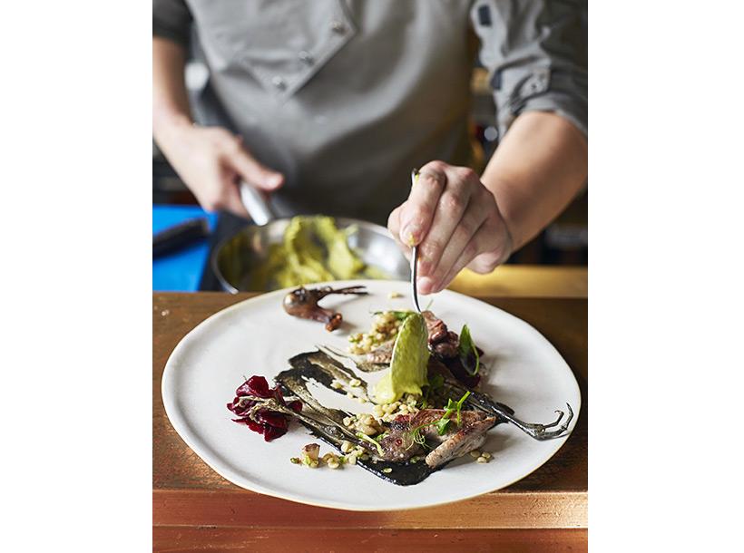chef plating up food artistically at Mecha Uma