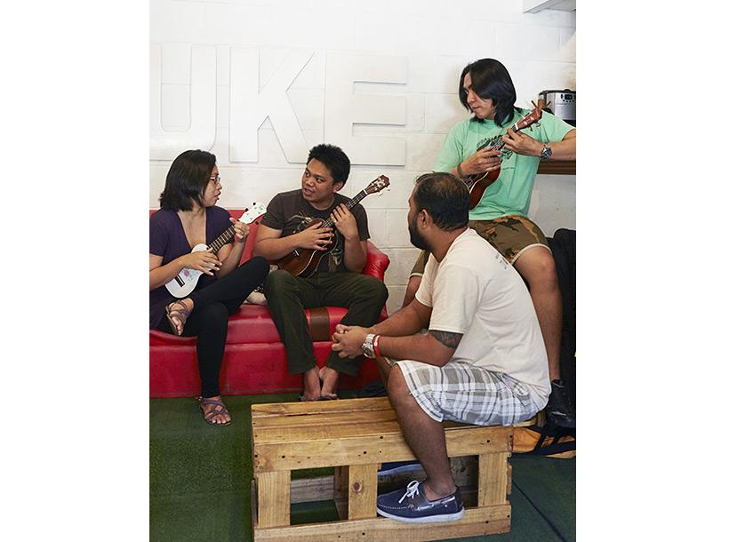 four people gathered, playing ukele's