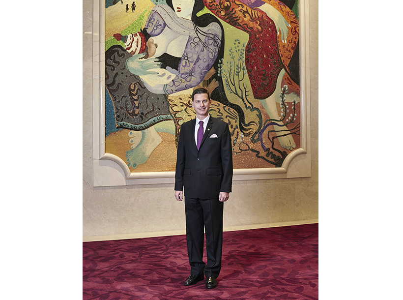 General Manager stands in front of large painting at Raffles Jakarta